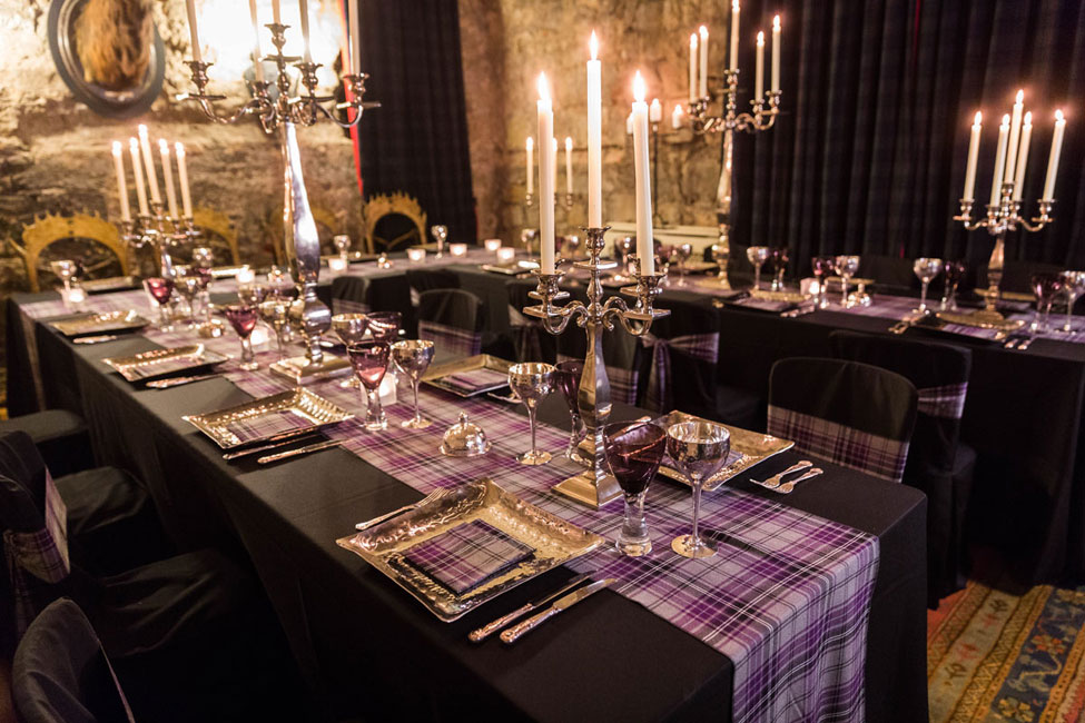 Black Essential table linen and chair covers paired with Ailsa Tartan set ties, Pewter charger plates with Ailsa Tartan napkin,Purple Chalice and Pewter Goblet, Silver Square Base Candelabra
