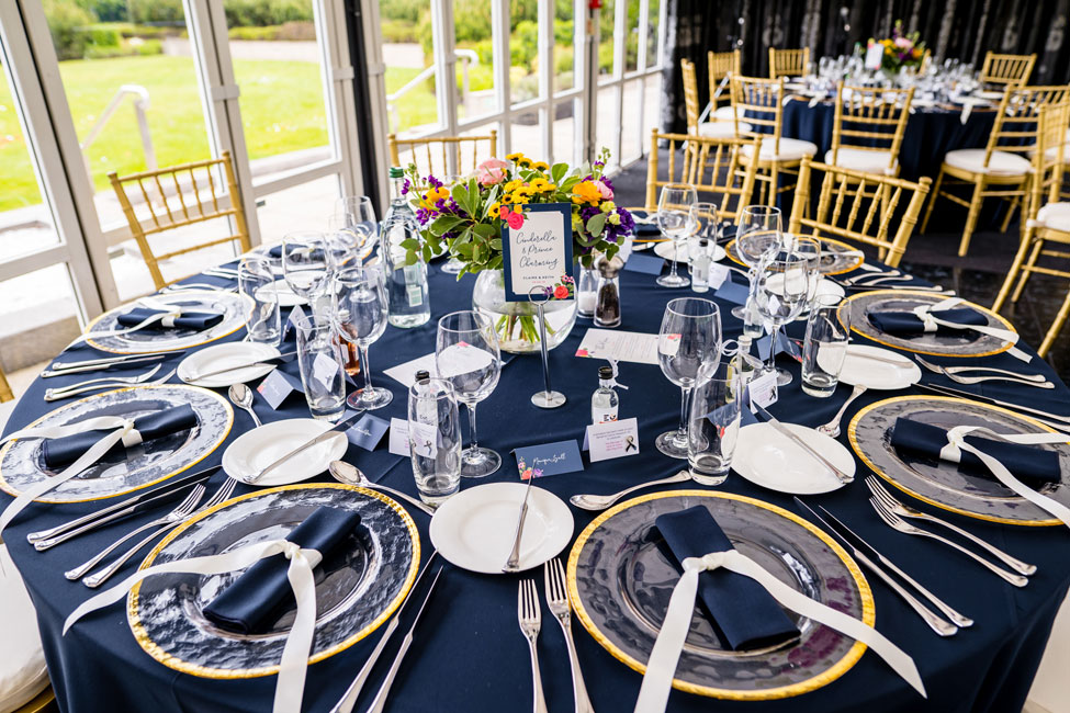 Navy Essential table linen, Gold Trim charger plates with Navy Essential napkin tied with ribbon