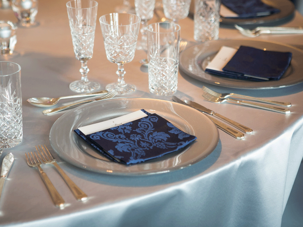 Silver Milano table linen, Silver charger plate paired with French Navy Vintage Damask napkin and Cut Crystal glassware