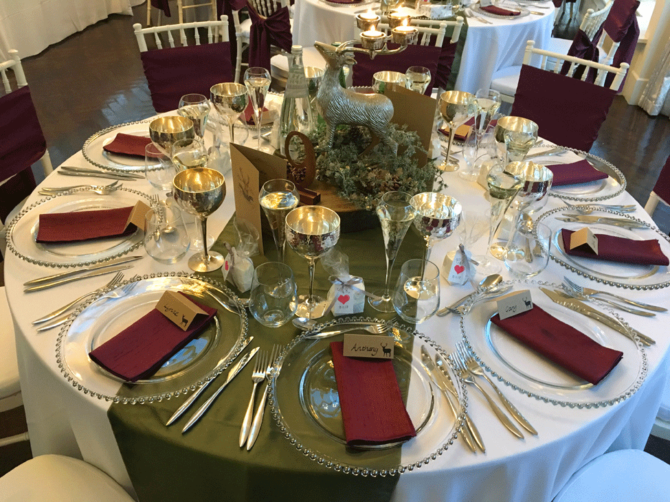 White Essential table linen, Woodland Taffeta runners,Silver Beaded charger plates paired with Plum Faux Silk napkins and Ivory Chiavari Chairs with White Essential Cushioned Seat Pads and Plum Faux Silk seat ties