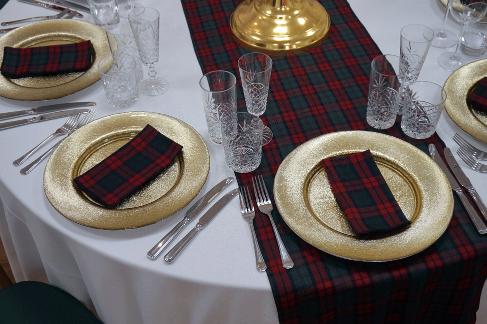 White Essential table linen, Lindsay Tartan runner and napkins, Gold Starburst charger plates paired with Cut Crystal glasses