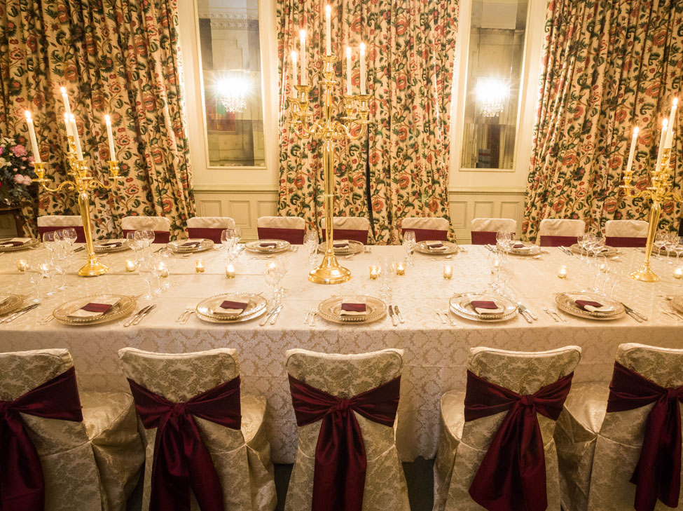 St. Tropez table linen and chair covers paired with Burgundy Taffeta seat ties and Gold candelabras