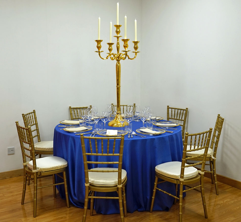 Electric Blue Faux Silk table linen, Gold Chiavari Chair with Vanilla Milano seat pads,Gold Candelabra, Gold Beaded charger plates paired with Vanilla Milano napkins