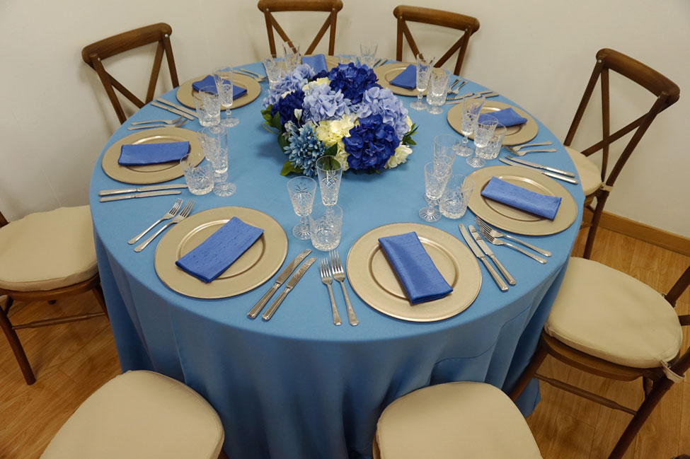 Wedgewood Essential table linen, Crossback Chairs with Biscuit Essential seat pads, Cut Crystal glasses, Latte charger plates paired with Electric Blue Faux Silk napkins