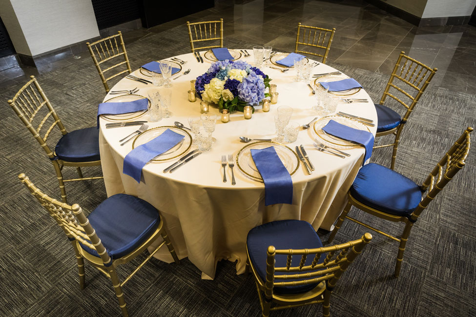 Styling featuring Nude Verona table linen, Gold Trim charger plates paired with Electric Blue Faux Silk napkins, Gold Chiavari Chairs with Midnight Blue Taffeta seat pads