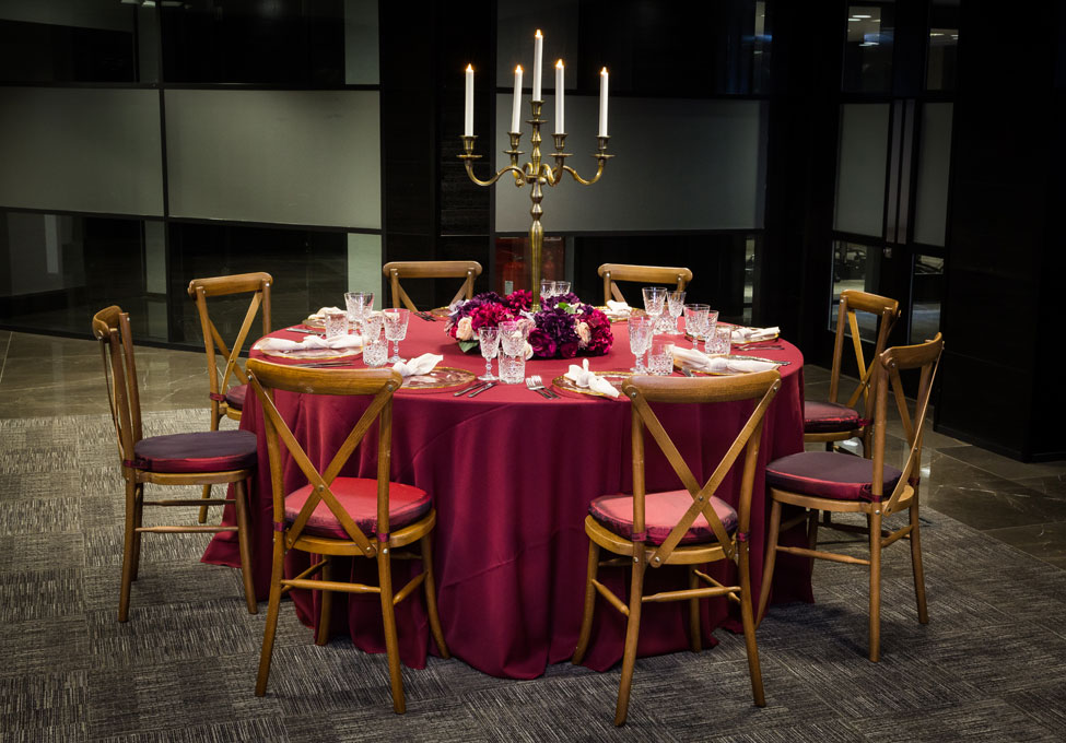 Styling featuring Wine Essential table linen, Gold Trim charger plates with Biscuit Essential napkins, Crossback Chairs with Burgundy Taffeta seat pads, Cut Crystal glasses and Rustic Bronze Candelabra