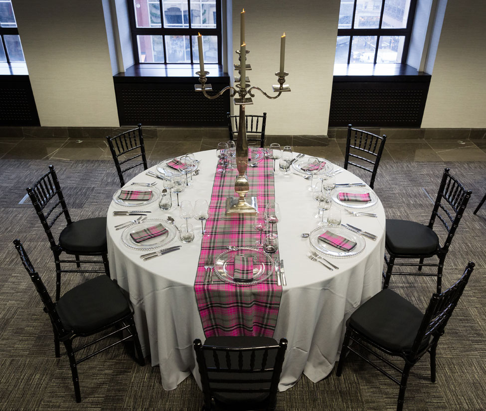 Styling featuring Grigio Gelato table linen, Silver Beaded charger plates paired with Iona Tartan napkins and table runner, Smoke Grey glasses, Silver Square Base Candelabra and Black Chiavari Chairs with Black Essential seat pads