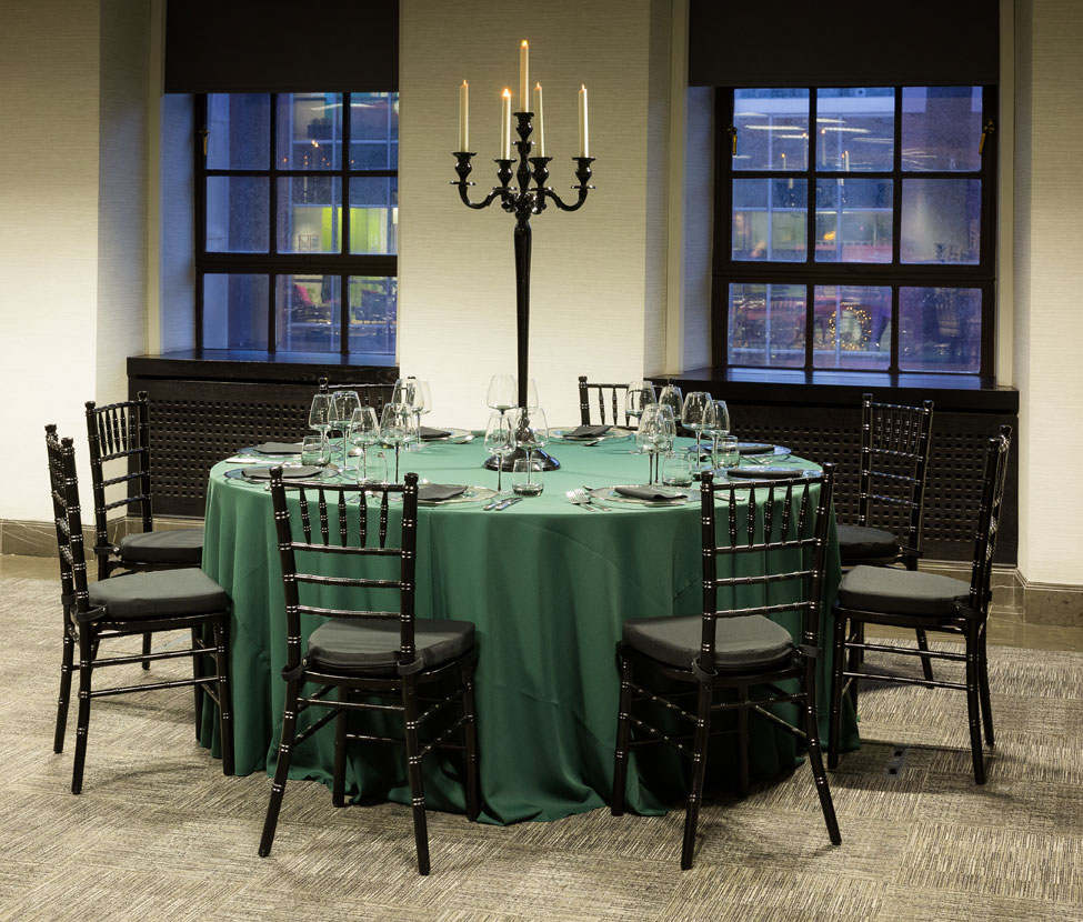 Styling featuring Green Essential table linen, Silver Trim charger plates paired with Black Essential napkins, Smoke Grey glasses, Black Gloss Candelabra and Black Chiavari Chairs with Black Essential seat pads