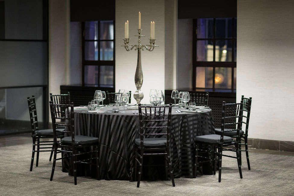 Styling featuring Black Chic table linen, Graphite Gelato napkins, Smoke Grey glasses, Silver Square Base Candelabra and Black Chiavari Chairs with Black Essential seat pads