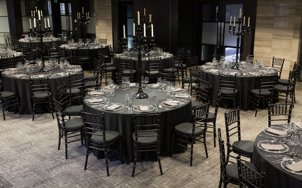 Styling featuring Black Essential table linen, Smoke Grey glasses, Silver Beaded charger plates paired with Graphite Gelato napkins, Black Gloss Candelabras and Black Chiavari Chairs with Black Essential seat pads.