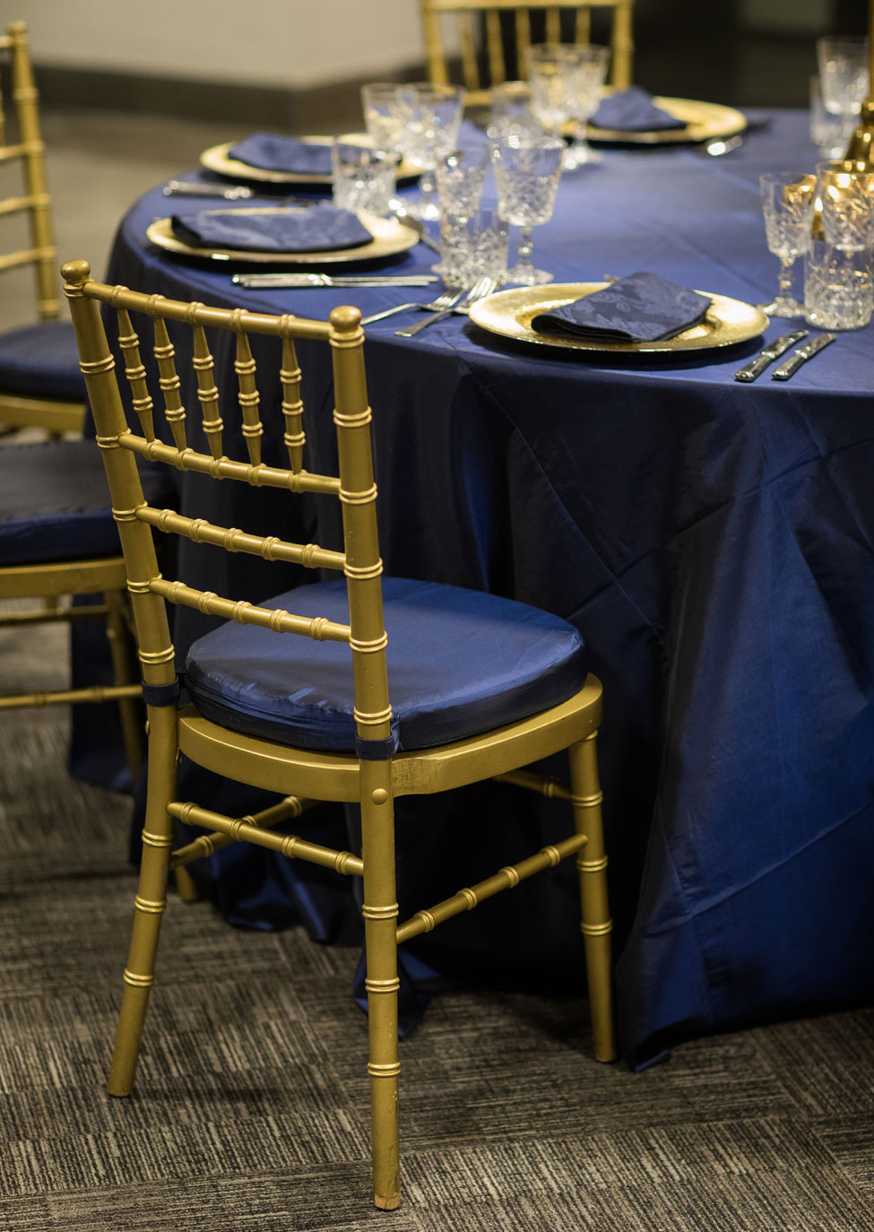 Styling featuring Midnight Blue Taffeta table linen, Gold Starburst charger plates paired with French Navy Vintage Damask napkins, Cut Crystal glasses, Gold Candelabra and Gold Chiavari Chairs with Midnight Blue Taffeta seat pads