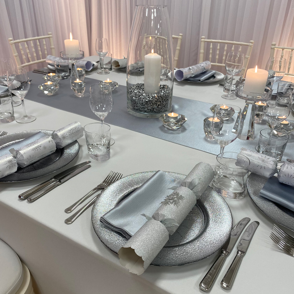 Styling features: Ivory Chiavari chairs w/white Essential pads, white Essential linen, silver Milano runner & napkins, silver Starburst chargers and Riedel glasses.