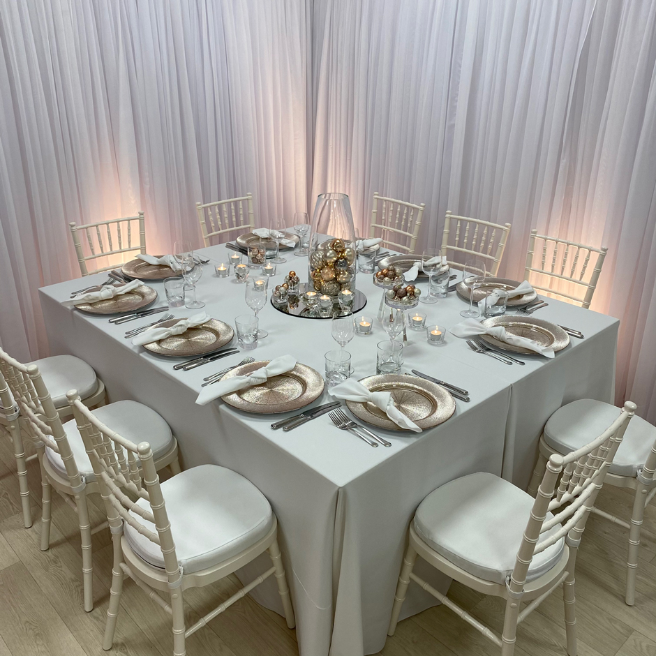 Styling features: Ivory Chiavari chairs w/white Essential pads, white Essential linen & napkins, rose gold Starburst chargers and Riedel glasses.