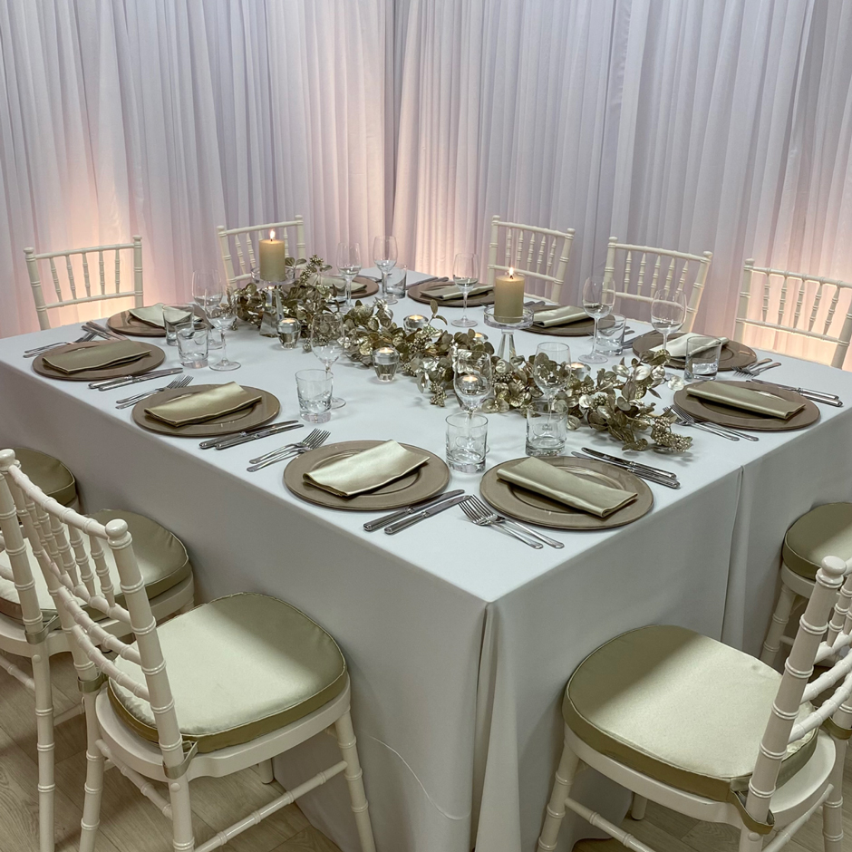 Styling features: Ivory Chiavari chairs w/sand Milano pads, white Essential linen, sand Milano napkins, latte Metallic chargers and Riedel glasses.