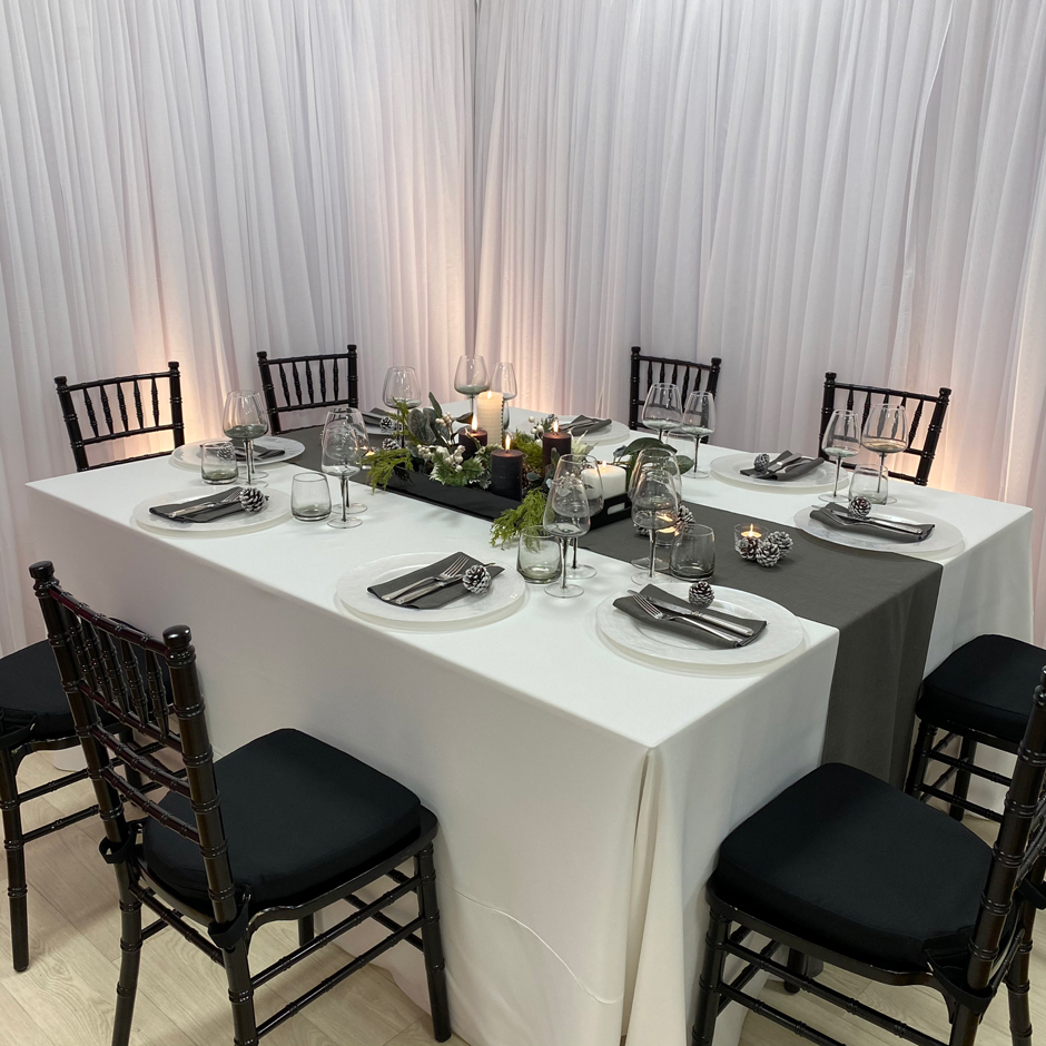 Styling features: Black Chiavari chairs w/black Essential pads, white Essential linen, graphite Gelato runner & napkins, Pearl chargers and Smoke Grey glasses.