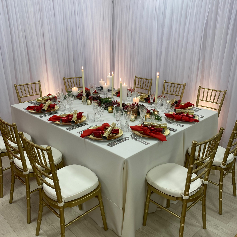 Styling features: Gold Chiavari chairs w/cream Essential pads, cream Essential linen, red Essential napkins, gold Starburst chargers and Cut Crystal glasses.