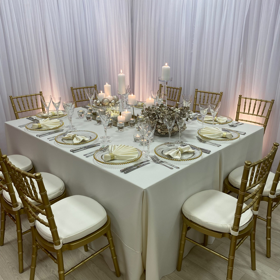 Styling features: Gold Chiavari chairs w/cream Essential pads, cream Essential linen, vanilla Milano fan & bow-tie napkins w/gold napkin rings, gold Beaded chargers and Swirl glasses.