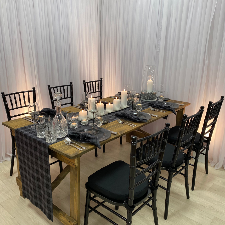 Styling features: Black Chiavari chairs w/black Essential pads, Arran tartan runner & napkins, Smoke Grey chargers & glasses.