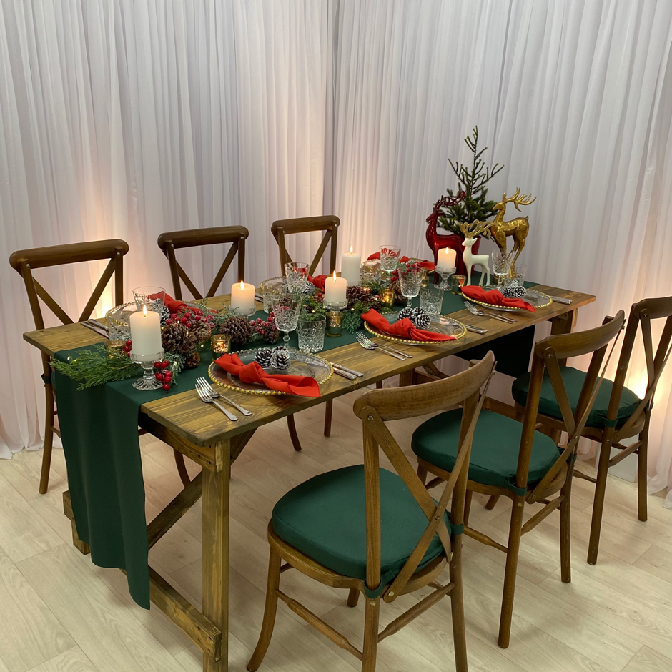 Styling features: Crossback chairs w/green Essential pads, green Essential runner, red Essential napkins, gold Beaded chargers & Cut Crystal glasses.